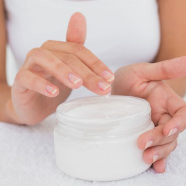 close-up-mid-section-of-woman-applying-cream-over-PJ88FD9.jpg