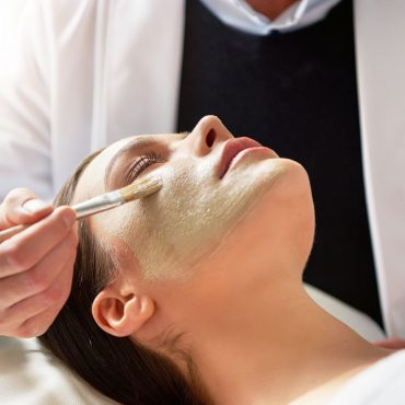 cosmetologist-putting-mask-on-female-face-with-8GWXHFP.jpg